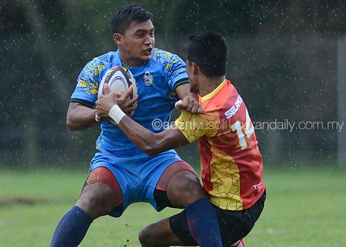 Pemain Selangor(merah/kuning) cuba menghalang lawannya dari pasukan Pulau Pinang dalam perlawanan pembukaan Divisyen 2 Kejohanan Ragbi Piala Agong 2018 Ke-36 yang berlangsung di Padang Utara, Petaling Jaya. Kredit Foto – Sukandaily